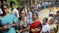 People stand in a queue to cast their vote during the re polling of votes at Ganeshpara in Guwahati on Sunday. (PTI)
