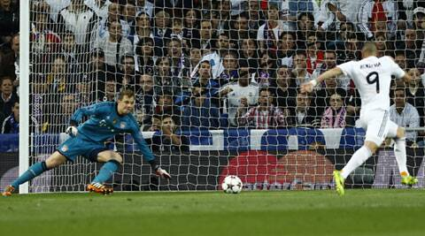 Real's Karim Benzema scores the opening goal past Bayern goalkeeper Manuel Neuer during a first leg semifinal Champions League soccer match between Real Madrid and Bayern Munich (AP)