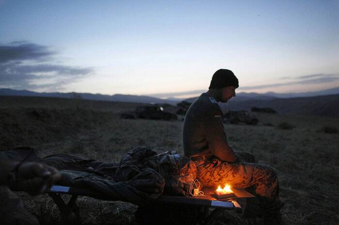 Anja Niedringhaus, 48, an internationally acclaimed German photographer, was killed instantly, according to an AP Television News freelancer who witnessed the shooting. <br /> A German soldier sits next to candles lit to celebrate his 34th birthday, during a long term patrol in Yaftal e Sofla, in the mountainous region of Feyzabad, east of Kunduz, Afghanistan, on September 16, 2009. (AP Photo/Anja Niedringhaus)