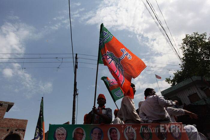 BJP supporters with party flags during an election roadshow in Bareilly. (IE Photo: Tashi Tobgyal)