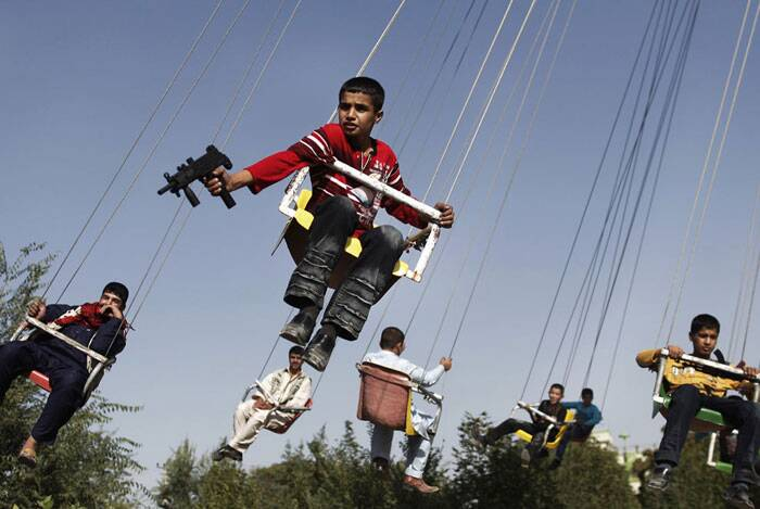 An Afghan boy holding a toy gun enjoys a ride with others on a merry-go-round to celebrate the Eid al-Fitr festival, in Kabul, on September 20, 2009. (AP Photo/Anja Niedringhaus, file)