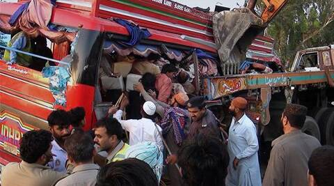 Pakistani rescue worker and volunteers gather to remove passengers from a damaged bus at the accident site. (AP)
