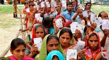 People show their I- Cards as they stand in a queue to cast their votes at a polling station for Lok Sabha elections in Chandigarh on Thursday. (PTI)
