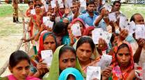 People show their I- Cards as they stand in a queue to cast their votes at a polling station for Lok Sabha elections in Chandigarh on Thursday.