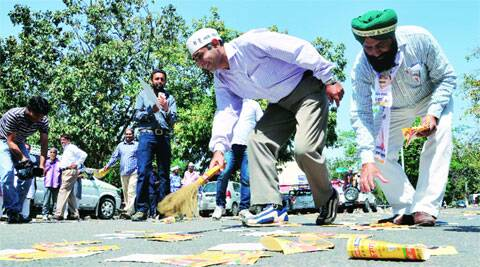 AAP workers sweep BJP party pamphlets away after the passing of Kirron Kher's convoy in Sector 7, Chandigarh, on Tuesday. Kshitij Mohan