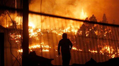 A man walks as an out of control forest fire destroys homes in the city of Valparaiso, Chile, Sunday. (AP)