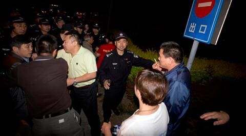 Chinese police men try to prevent relatives of Chinese passengers onboard the Malaysia Airlines MH370 from marching to the Malaysian embassy from a hotel in Beijing, China on Thursday. (AP)