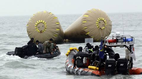 South Korean rescue members search passengers believed to have been trapped in the sunken ferry Sewol. (AP)
