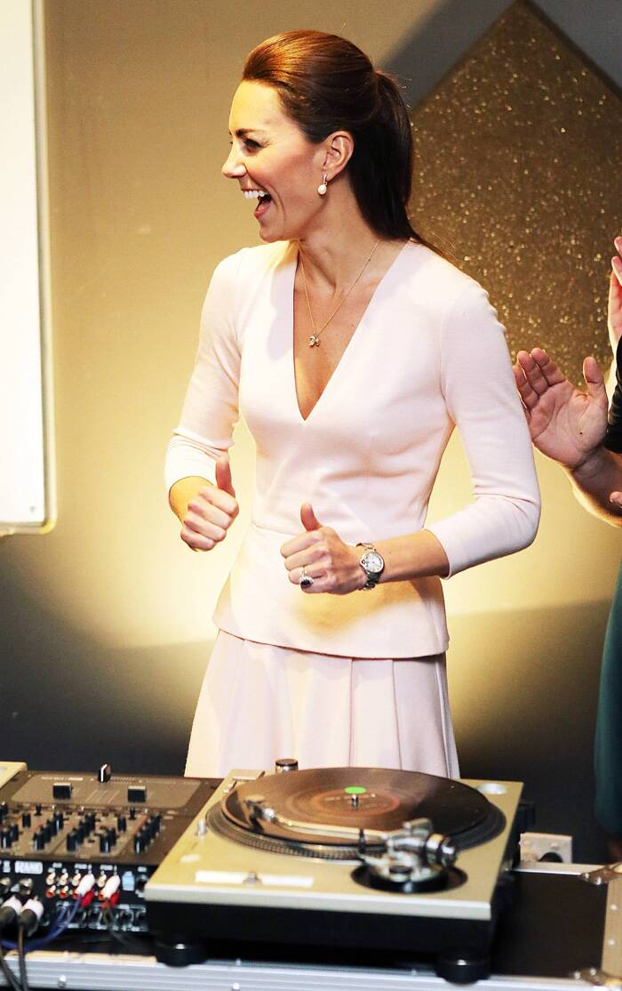 The Duchess of Cambridge gestures after she used the DJ decks. (Reuters)