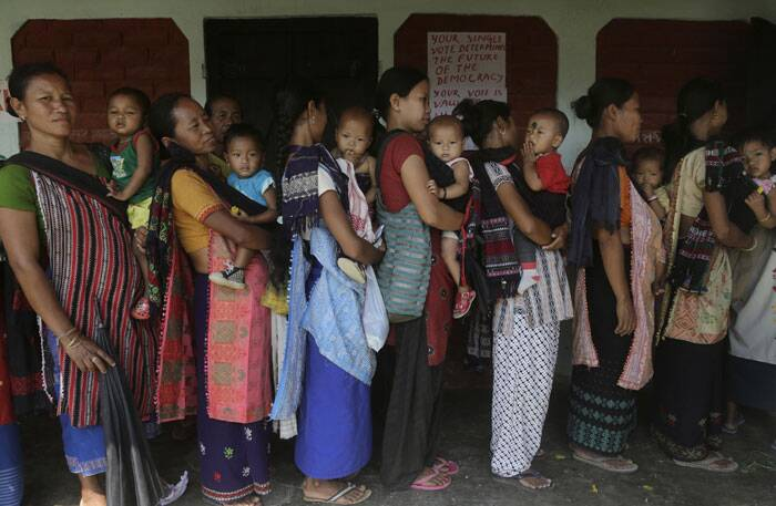 Karbi tribal women in traditional outfits carry their babies and stand in a queue to cast their votes, outside a voting center in Diphu, Assam on Saturday. (AP)