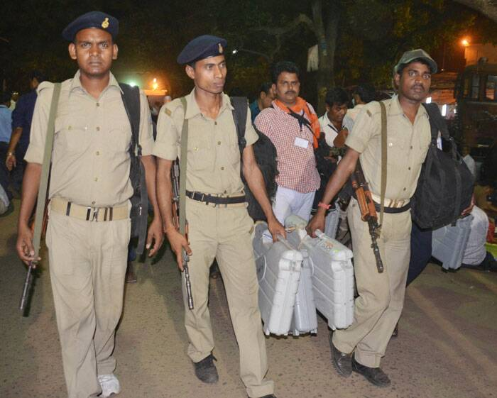 Policemen with EVMs at the end of voting for Lok Sabha polls at a polling station in Dhanbad on Thursday. (PTI)