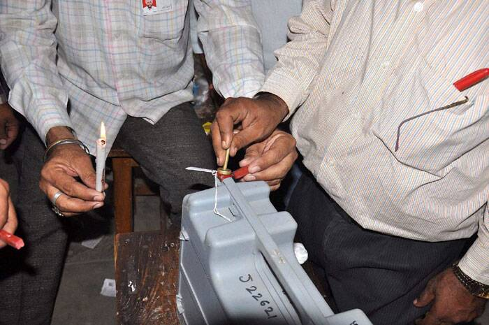 Polling officials seal an EVM at the end of voting for Lok Sabha polls at a polling station in Mathura on Thursday. (PTI)