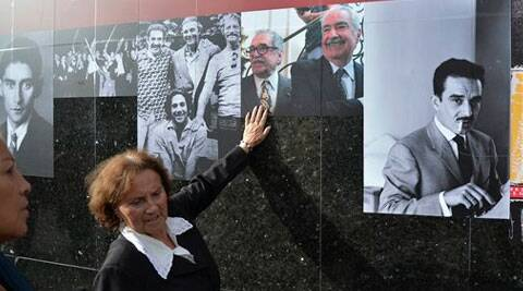 A woman touches photos on a timeline of the life of Colombian Nobel laureate Gabriel Garcia Marquez on a wall at the Luis Angel Arango Library in downtown Bogota, Colombia, Thursday, April 17, 2014. Garcia Marquez died in Mexico City on Thursday