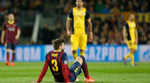 Barcelona's Gerard Pique sits on the pitch after injuring himself during a first leg quarterfinal Champions League soccer match between Barcelona and Atletico Madrid at the Camp Nou stadium in Barcelona (AP)