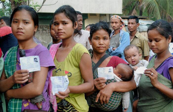 In Shillong a total eight contestants are in the fray, including the sitting Congress MP Vincent Pala, UDP candidate former student leader Paul Lyngdoh, BJP nominee Shibun Lyngdoh besides church leader P B M Basaiawmoit, who is fighting as an independent. <br /> People show their voter identity card as they queue to cast their vote at a polling booth at Ri Bhoi area, in Meghalaya on Wednesday. (PTI)