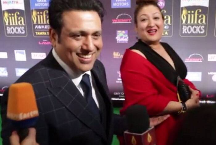 Govinda and his wife Sunita stop to speak to the media as they arrive on the green carpet. The actor will unveil his film 'Abhinay Chakra' at IIFA this year. (Twitter)