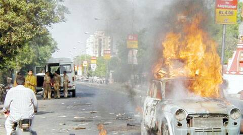 File photo: A man rides past a burning car during a riot in Ahmedabad, Gujarat, May 5, 2002. (Photo: Reuters)