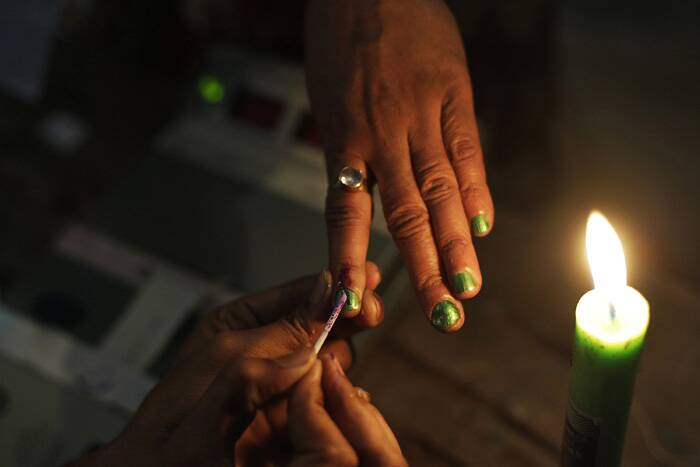A polling official ink marks the index finger of a woman voter in Gauhati. (AP)