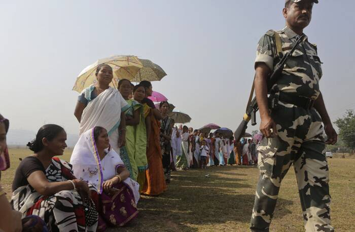 A security person stands guard as women wait in a queue to cast their votes in Gauhati. (AP)