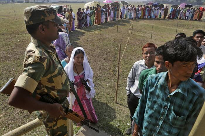 A security person stands guard as people wait in a queue to cast their votes in Sonapur village, outskirts of Gauhati. (AP)