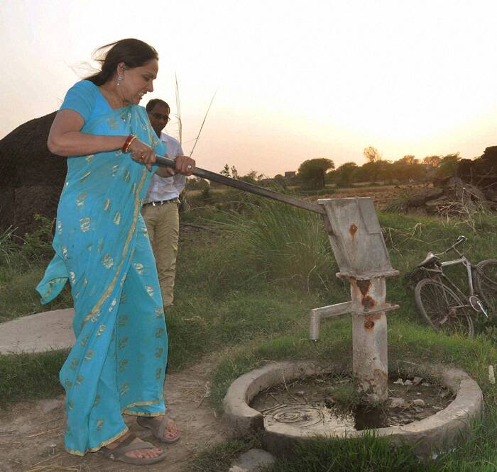 Hema Malini operates a hand pump at a village during her election campaign in Mathura. (PTI)