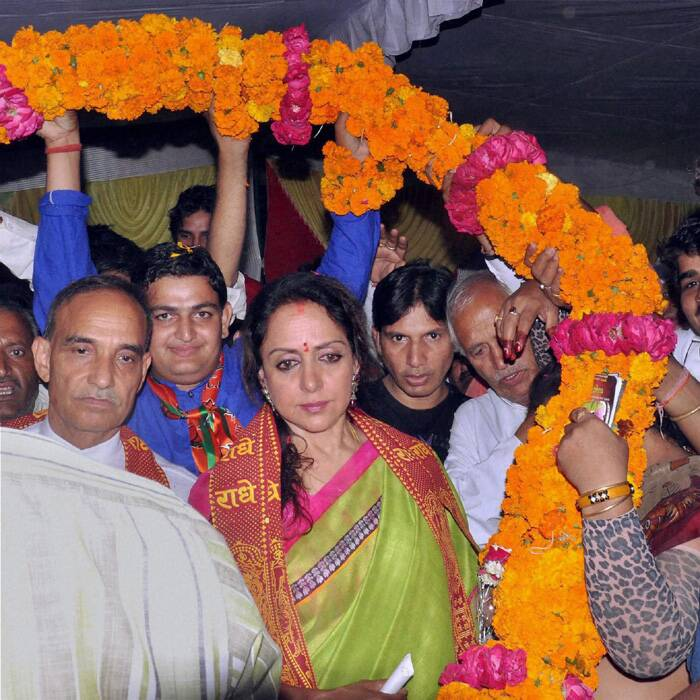 Bollywood actress & BJP candidate Hema Malini along with former Mumbai police commissioner and BJP candidate Satyapal Singh Yadav garlanded during her election campaign in Mathura. (PTI)
