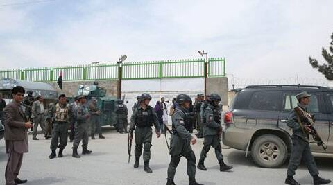 Afghan police forces walk in front of the main gate of Cure International Hospital in Kabul, Afghanistan on Thursday (AP)
