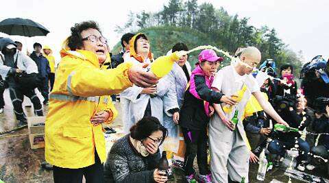 Relatives perform a ceremony to pray for safety of passengers in Jindo Thursday