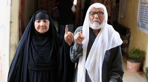 A man and his wife show their inked fingers after casting their votes for parliamentary elections at a polling in Baghdad, Iraq. (AP)