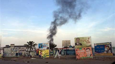 Smoke rises above campaign posters after a series of bombs that exploded on Friday in Baghdad, Iraq. The blasts killed and wounded dozens. (AP)