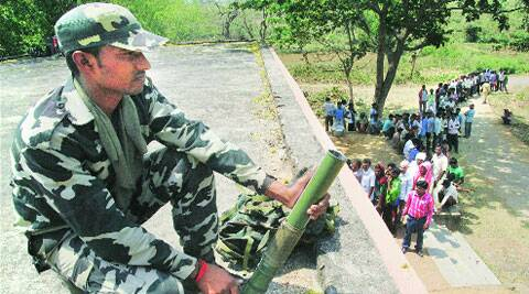 A jawan keeps vigil while people stand in queue at a polling station at Gobindpur.PTI