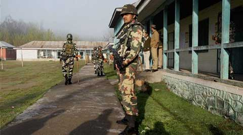 Security personnel stand guard at a polling station, wearing deserted look, in Pulwama on Thursday. (PTI)