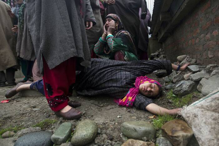 A relative of Zia-Ul-Haq lays unconscious on ground as others wail during Zia's funeral procession in Shopian. (AP)