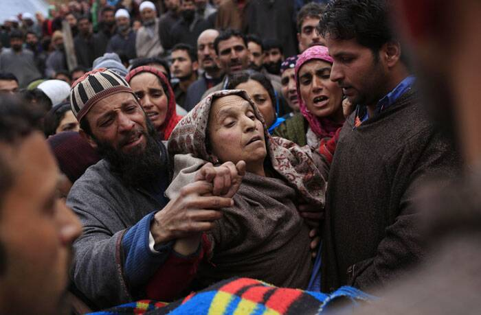 Unidentified villagers comfort Hanifa Beigam, the grieving mother of Zia-Ul-Haq,  during his funeral procession. (AP)