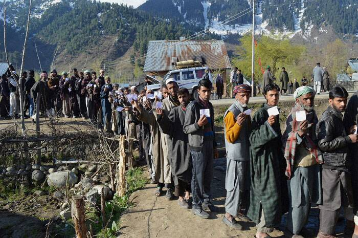 Voters queue up to cast their votes  at a polling station in Aharbal village in Kulgam on Thursday. (PTI)