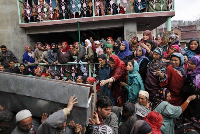 A Kashmiri Muslim woman, center wearing a red scarf, tries to reach out to the coffin of Zia-Ul-Haq during the his funeral procession in Shopian. (AP)