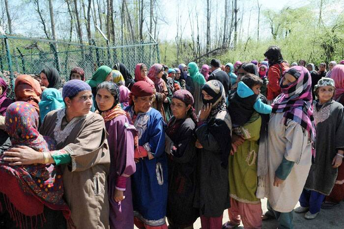 Women voters queue up to cast their votes  at a polling station at a village in Kulgam on Thursday. (PTI)