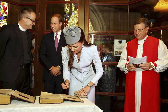 Kate Middleton signs the First Fleet Bible and Prayer Book as Prince William and The Most Reverend Glenn Davies, Archbishop of Sydney look on. (AP)