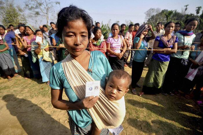 A woman voter carries her kid as others wait to cast votes for Tripura West Lok Sabha polls outside a polling station in Dhamcherra on Saturday. (PTI)