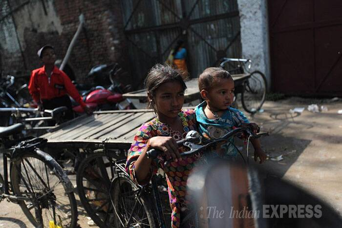 A young girl with her sibling watches a BJP election road show in Bareilly. (IE Photo: Tashi Tobgyal)