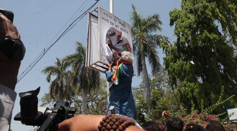 Madhusudan Mistry climbs up the pole to replace Narendra Modi's poster with Congress campaign material. (IE)