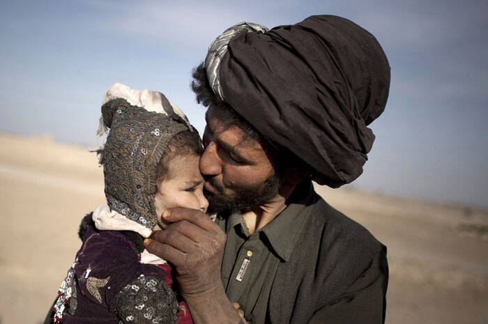 An Afghan nomad kisses his young daughter while watching his herd in Marjah, Helmand province, on October 20, 2012. In southern Helmand province, one of Afghanistan's deadliest battlefields, angry residents say 11 years of war has brought them widespread insecurity. They say they are too afraid to go out after dark because of marauding bands of thieves and during the day corrupt police and government officials bully them into paying bribes. Development that was promised hasn't materialized and the Taliban's rule is often said to be preferred. (AP Photo/Anja Niedringhaus)
