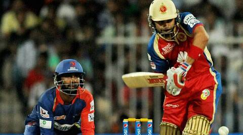 Royal Challengers Bangalore captain Virat Kohli plays a shot as Delhi Dardevils wicket-keeper and skipper Dinesh Karthik looks behind the stumps. (PTI)
