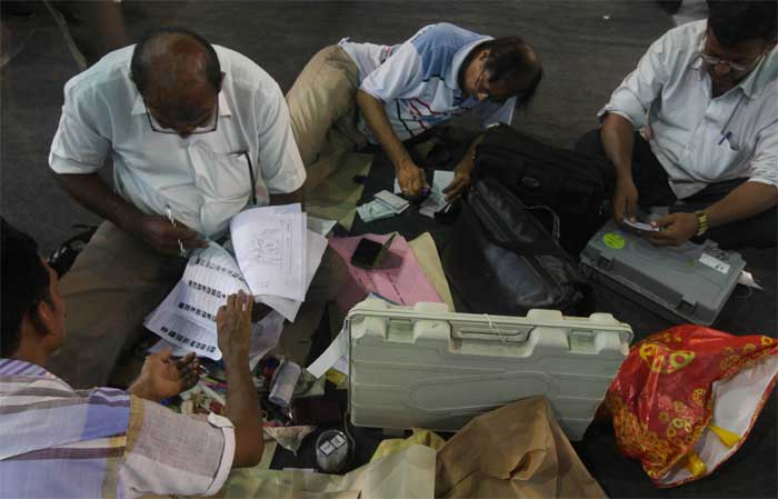 Election officials checking election materials before departure to their destination  on the eve of 3rd phase Parliamentary elections at Dumurjala stadium in Howrah. (Express Photo: Partha Paul)