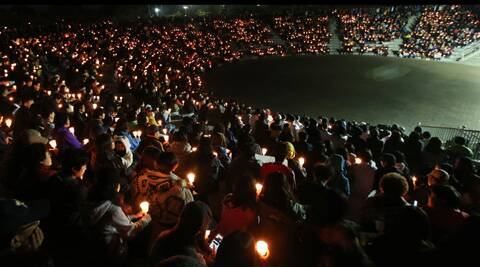 Danwon high school students and citizens hold candles as they pray for the safe return of passengers of the sunken Sewol ferry in Ansan, South Korea. (AP)