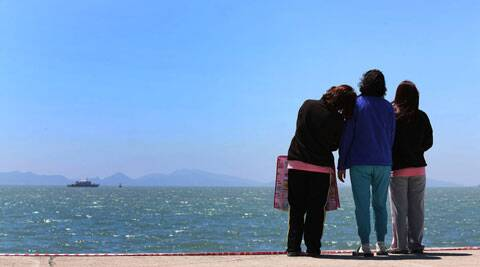 Relatives of a passenger aboard the sunken Sewol ferry look toward the sea at a port in Jindo, South Korea. (AP)