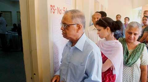 Infosys Executive Chairman N R Narayana Murthy with daughter Akshata and wife Sudha Murthy standing in a queue to cast their votes for Lok Sabha elections at a polling booth in Jayanagara in Bengaluru. (PTI Photo)