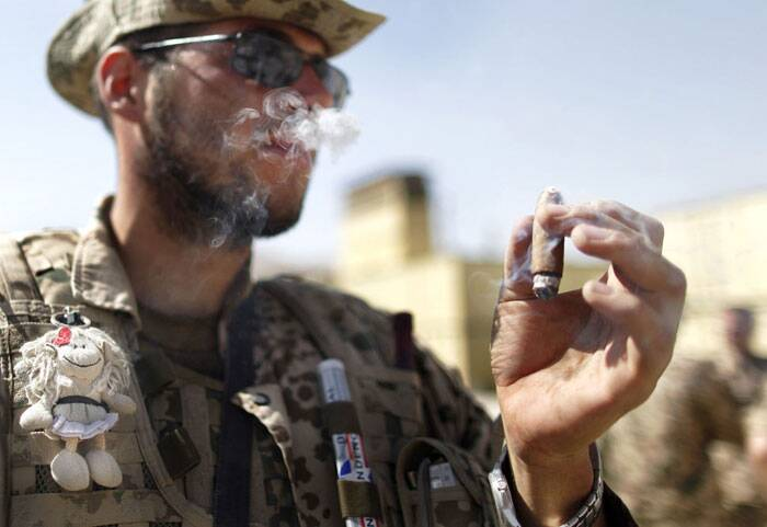 A German ISAF soldier, bearing a lucky charm attached on his bulletproof vest, enjoys a cigar after arriving with his unit back to the base in Feyzabad, east of Kunduz, on September 11, 2009. The unit was stuck for days in the area of Kunduz and came under heavy fire in which four soldiers where injured and evacuated to the field hospital in Kunduz. (AP Photo/Anja Niedringhaus)