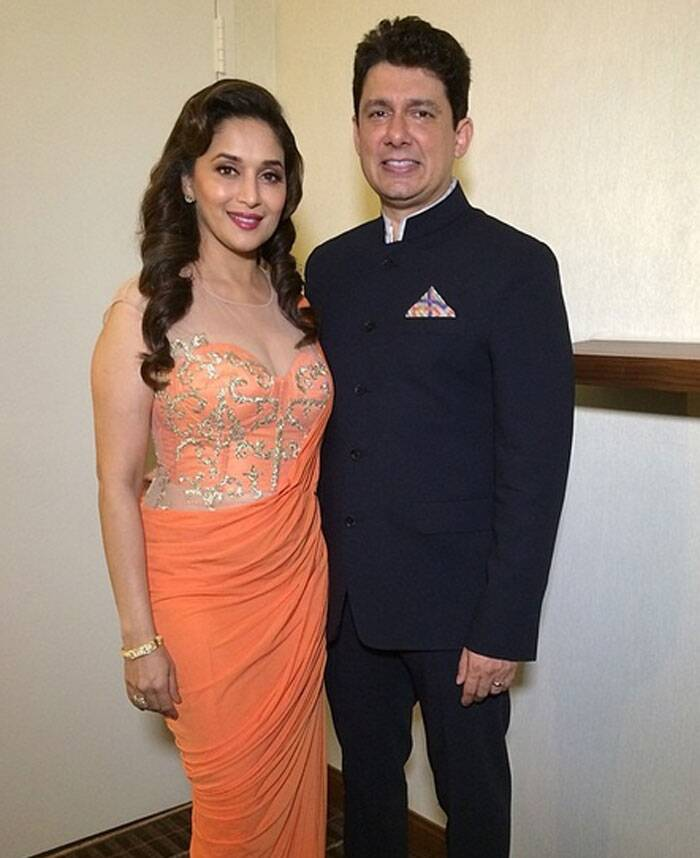 Madhuri Dixit looked nice in a sheer orange outfit as she posed along with husband Dr. Sriram Nene for pictures. (Twitter)