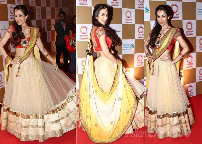 Yummy mummy Malaika Arora Khan was gorgeous as she showed off her midriff twirling on red carpet in a red choli with a gold lehenga. (Photo: Varinder Chawla)